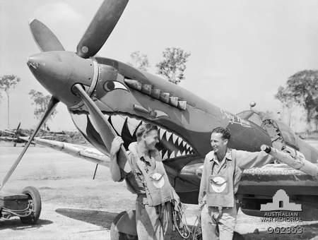 "Flying Officer K. B. May, Rockhampton, Qld, and Fl Sgt R. Blacklock, Brisbane, Qld, of 457 ""Grey Nurse"" Sqn RAAF, First Tactical Air Force in front of a Spitfire Mk VIII bearing the squadron's shark jaws insignia. Note the sharks painted on the Mae West life jackets and the faded ""eye"" from an earlier version of the insignia which can be viewed in the Australian Forces section, 4 pages forward of the last page. Morotai, Halmahera Islands, Netherlands East Indies. Apr-1945"