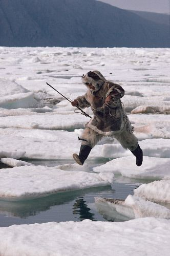 Inuit hunter, Kavavow Kiguktak, jumps from one ice floe to another. Ellesmere Is., Nunavut, Canada.
