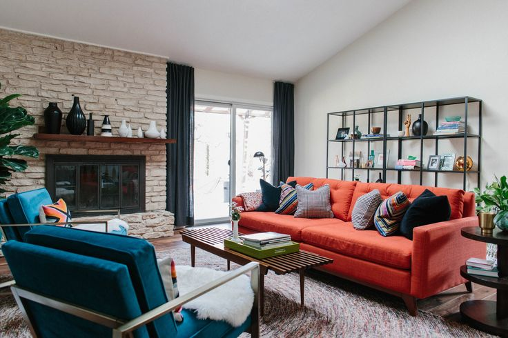 The open and inviting living room has pops of color. The well-styled black shelf is the IKEA Vittsjo.