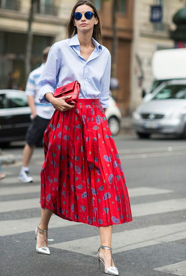 inspiração street style saia mídi vermelha plissada, camisa azul, clutch vermelha, scarpin prata, óculos de sol lentes espelhadas azuis: