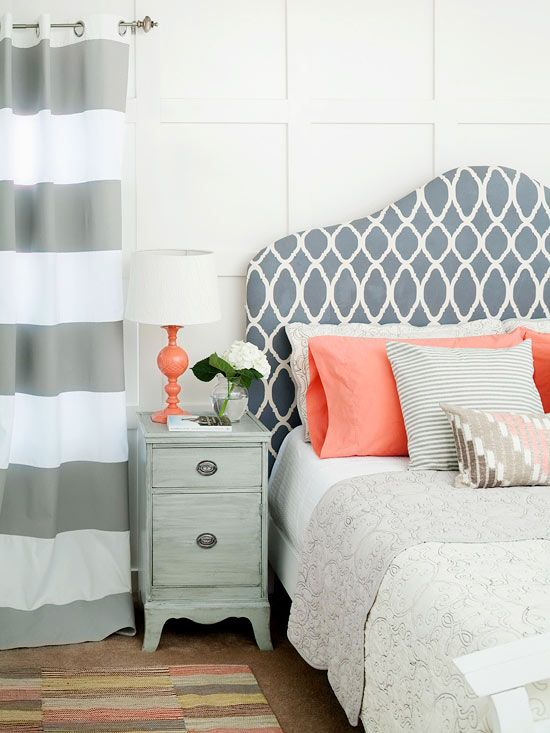 A patterned, fabric covered headboard says style against white walls. Wide striped draperies infuse the room with another layer of pattern, but they don't steal attention away from the headboard. Coral accents throughout the
