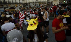 Spanish fans play the highly addictive Pokemon Go game during a gathering in central Madrid, Spain to play the computer game.
