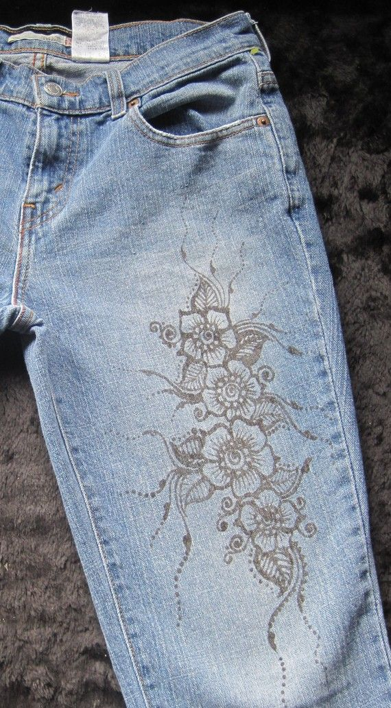 Mehndi/Henna painted design on a gently used pair of Levis jeans, size 4. Brown floral design trails up the left thigh and hip - very feminine and