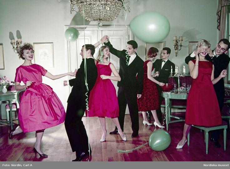 Fyra unga kvinnor i aftonklänningar i cerise nyans dansar och pratar med fyra unga män i svarta kostymer i en salong med gröna ballonger och uppdukade bord. Fotograf: Carl A Nordin, 1960-1965