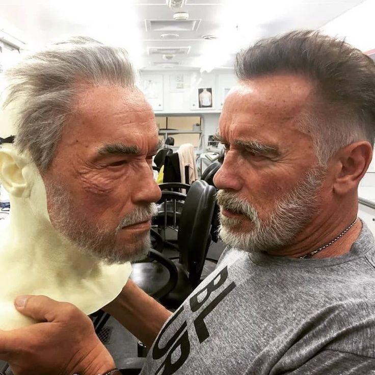 Arnold schwarzenegger holding a lifelike stunt double mask