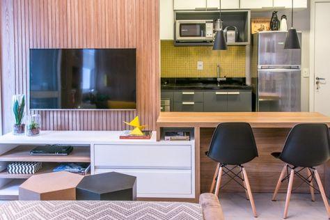 Sala de estar com cozinha integrada, painel de tv ripado, móvel de tv branco, bancada de refeições rápidas, cadeira eames, pastilhas amarelas, mesa de apoio hexagonal. Reforma e decoração apto completo, Apartamento de solteiro. Arquiteta Danyela Corrêa