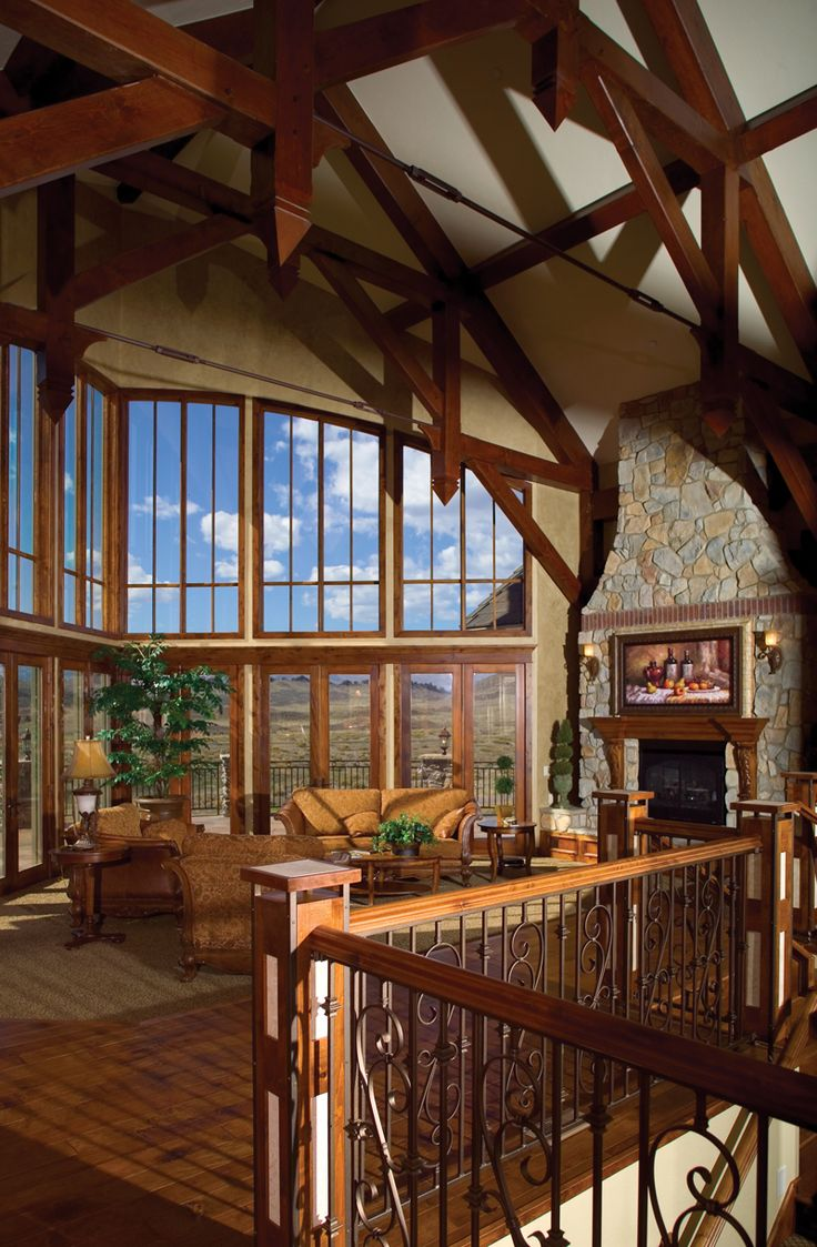 Rustic lodge style great room is topped with wood beams for Home plans with vaulted ceilings