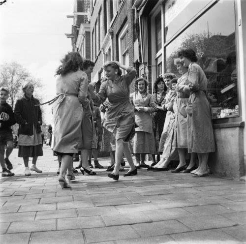 """Amsterdam, Dansende meisjes in de middagpauze voor platenzaak """"de Draaitafel"""" op de Lindengracht, 1958. (foto Kors van Bennekom)."""