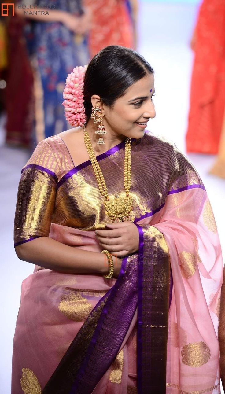 Vidya Balan in a silk big border saree and blouse. She teamed it with statement gold necklace and earrings. Hair in a slick bun and fresh flowers. Indian Bollywood fashion.