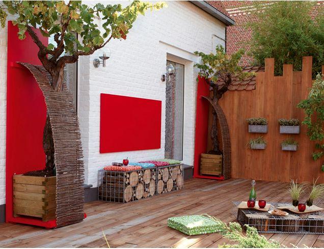 Pour prolonger le salon dans lequel le bois et le rouge sont en bonne place, la déco de la terrasse est pensée autour d'un parquet en pin pour faire écho à sol intérieur. Un jeu de verticales et horizontales en bois peint de rouge met en scène la banquette et les deux pieds de vigne. Les coussins verts jouent les complémentaires aux couleurs chaudes de cette terrasse et invitent au farniente.