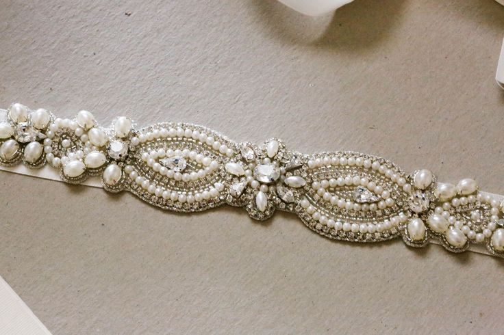 Bridal belt - Valeria v2 * Narrow bridal sash in silver, ivory and offwhite tone. The larger pearls are mostly white and smaller pearls are ivory. * Width = 1.25 inches * Length = 10 inches The beadin