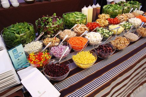 Chefs tossed various fresh items in front of guests at a salad bar.