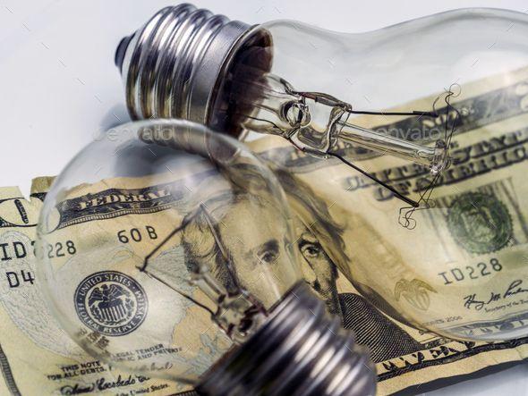 A lightbulb on dollar bill, energy saving concept …