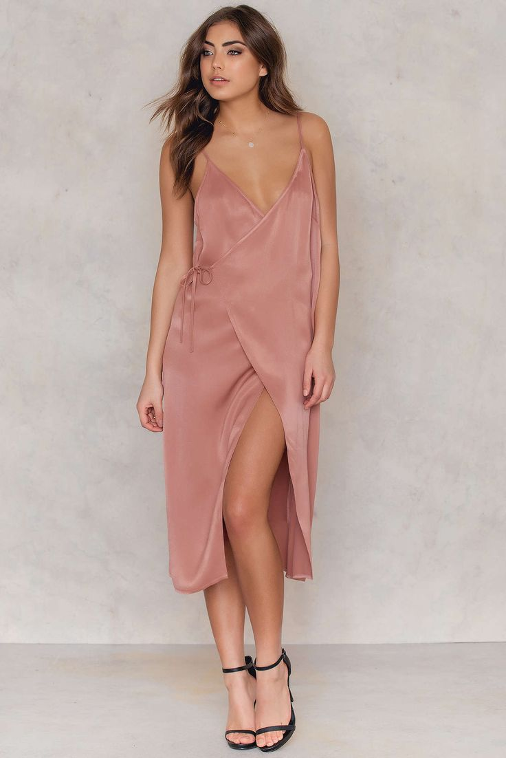 We've got a new twist on the slip dress trend! The Wrap Over Slip Midi Dress by Tranloev comes in the color dark blush and features thin adjustable straps, soft silk-like material, a v-neck front, a midi below-the-knee length, and two tie straps (one inside the dress and one outside), creating a wrap around style. Pair with sexy pumps and a thin black choker!