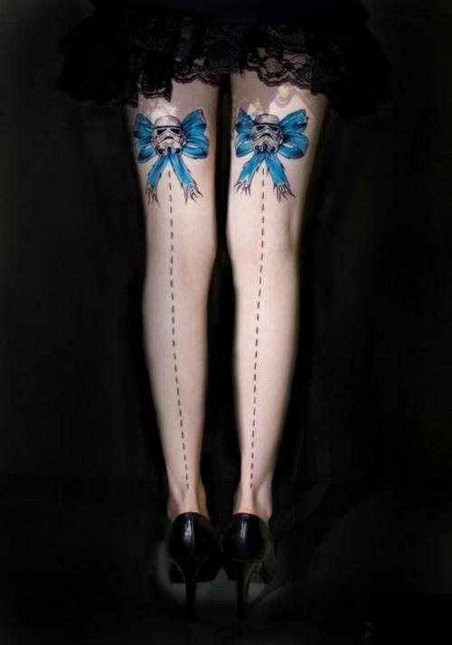 Photo de tatouage à l'arrière des jambe de noeud bleu et casque de Stormtrooper.