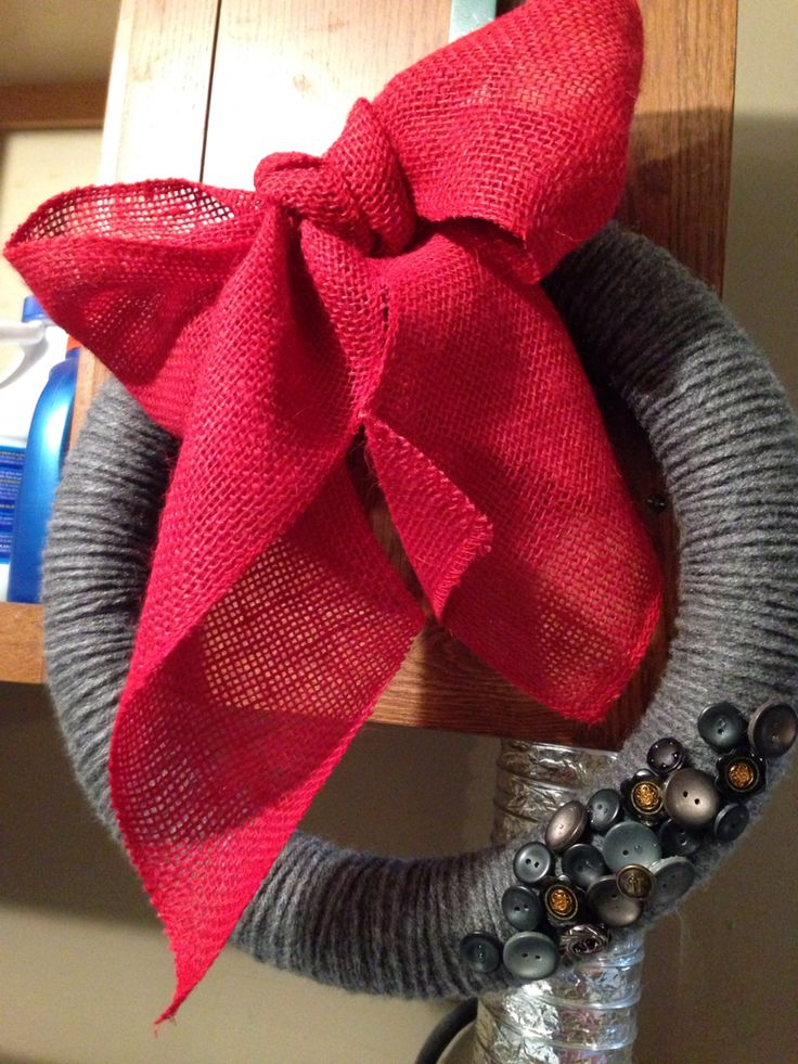 Yarn wrapped wreath with red burlap bow and button accent.