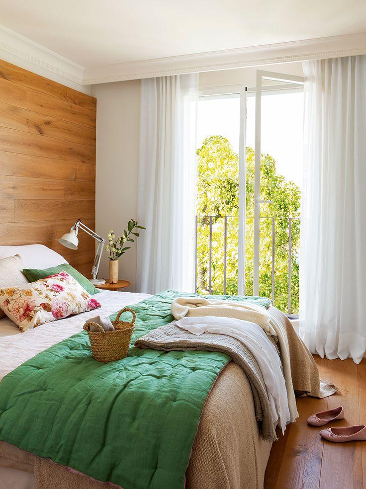 Dormitorio con pared del cabecero forrada en madera y balcón