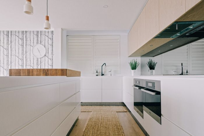 baxter+thrum Bayview Residence Handless drawers in white with timber upper cabinetry. #handlelessdrawers #modernkitchen