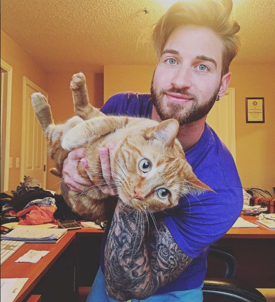 Travis DesLaurier is a sexy tattooed model that loves working out with his cute pet kitty cat. See all the adorable photos in this gallery.