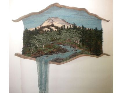 "This  large weaving will command any room, drawing the viewer into the forest  in the shadow of the majestic mountain. Yellow wildflowers dot the  riverside under the alders in this spring landscape. 31""x52"" +20"" waterfall.  MT JEFFERSON (20-49)  CLICK HERE FOR A LARGER IMAGE"