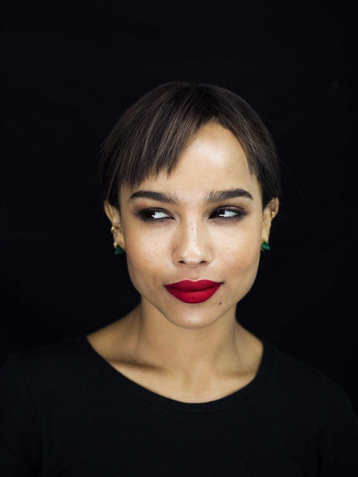 red lips, black matte background, emerald earrings, hair pulled back