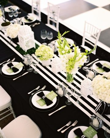 Long tables covered with black linens and striped runners were adorned with simple arrangements of hydrangeas, gladiolas, roses, and peonies