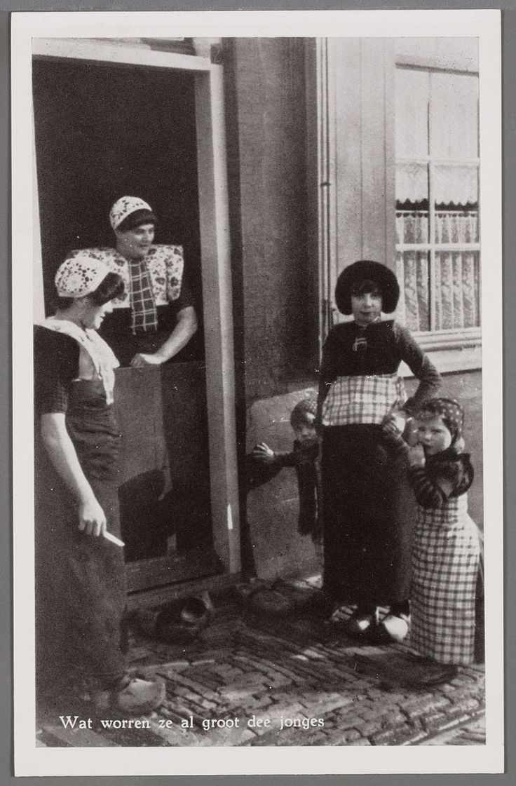 Links een vrouw van opzij gezien, met gehaakte muts en kuif, wit gebloemde kraplap, donkere geruite boormouwtjes en donker schort zonder stukje. Achter de onderdeur een vrouw met gehaakte muts, wit gebloemde brede kraplap met gedeelde rode doek. Rechts een meisje met pluummuts, jak en schort met geruit stukje. Aan de hand twee jongetjes in de rokken met klapmuts en gebreide mofjes. 1950-1960 #Utrecht #Spakenburg