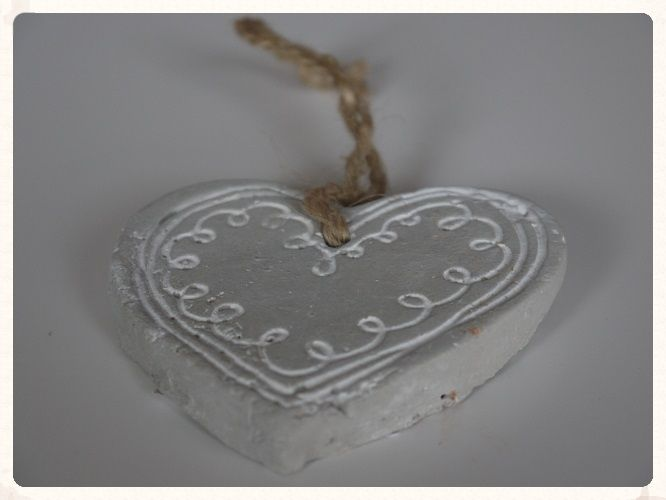 A small grey ceramic hanging heart decoration with a white swirl pattern and string handle Perfect to hang around your wedding venue or the ends of