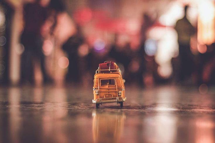 #action #architecture #blurred background #building #car #city #defocused #evening #light #luggage #nostalgic #outdoors #pavement #reflection #street #summer #sunset #toy car #travel #vehicle #water #yellow