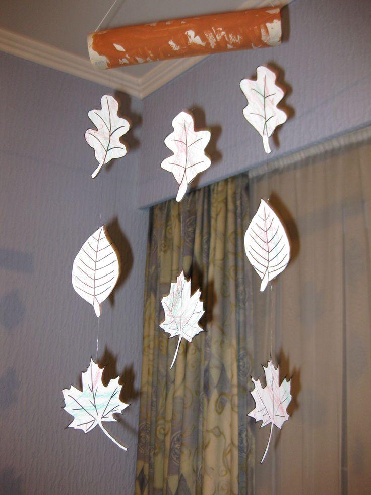 Tekeningen van bladeren laten inkleuren en deze aan een geverfde keukenrol vastmaken met visdraad