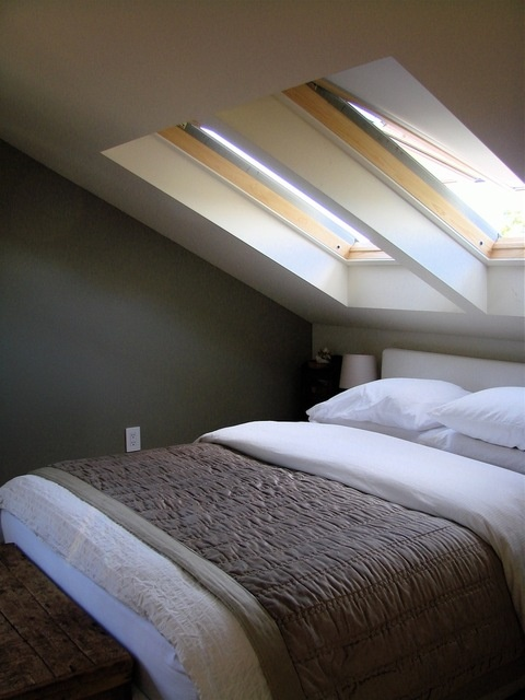 Skylights in slanted ceiling over bed.  I can't make up my mind if this setup would be super cool or really annoying...