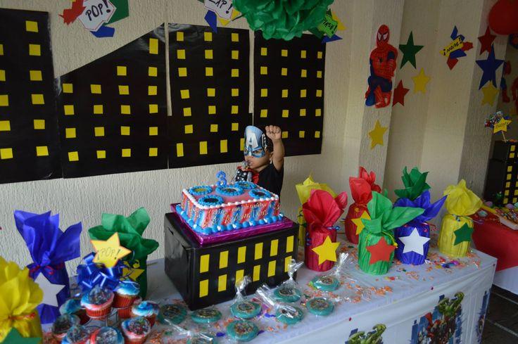 Mesa principal con sorpresas forradas en papel cometa, extrellas en cartulina de colores, pompones, torta, galletas.