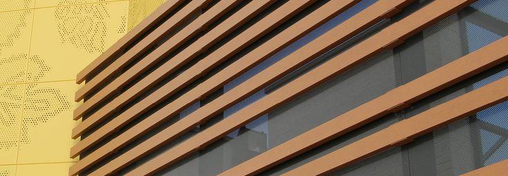 HABILLAGE DE FAÇADE Carrefour, HAZEBROUCK (59) Architecte : ASE PRODUCT Architectes Pose : Isobac Acier (59) Lames clippables de forme rectangulaire HF42x100 (coloris imitation bois RO 303 L). Fixation invisible.