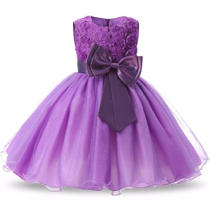 Feestelijke lila jurk met bloemetjeskant, grote sierstrik op het voorpand en aanknooplint op het achterpand. De rok bestaat uit twee lagen glitter-organza, een polyester onderlaag en daaronder een polyester binnenrokje. Knie- kuitlengte.  Model: Manon