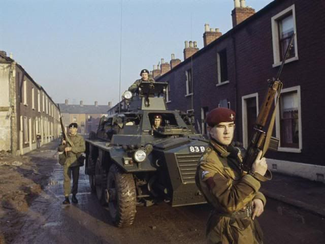 Second Lieutenant David Brough, 1st Battalion, The Parachute Regiment and Lance Corporal Bernard Winter, Second Battalion, The Queen's Regiment, patrol a Belfast street with a Saracen armoured personnel carrier. The Queen's Regiment was the first to be deployed in Belfast on 15 August 1969