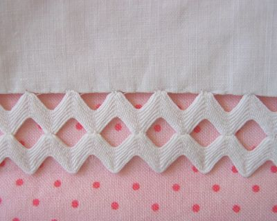 Two rows of rickrack attached along the edge with tiny tacking stitches at the points