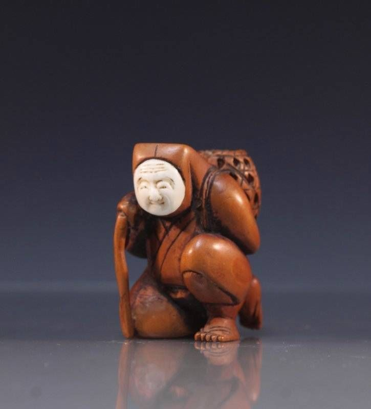 Japanese delicately carved detailed wood netsuke, featuring a man with carved face on his knee carrying a basket on his back, Late 19th century period. Size; Height of this fine carving is 1 7/8 inches. Condition Report; Great condition, no imperfections. Provenance: Property from the Collection of Dr. J. Don Nelson, Fargo, North Dakota.