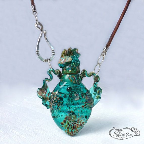 A richly textured, handmade, lampwork glass bottle necklace in teal green. I have crafted this little lampwork glass bottle from a gorgeous transparent teal green glass. It is decorated with speckles of a special silver rich reactive glass that changes in the heat of the flame to give a rainbow of ochre, purple, blue and green. Deep swirls, flowing ribbon handles and raised encased flowers add to the organic shape and rich texture, and a hand forged Argentium hook and leather cord complete…