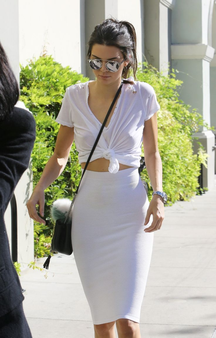 Kendall Jenner makes an impromptu crop to out of tying a white tee and pairing it with a white high-waisted pencil skirt.
