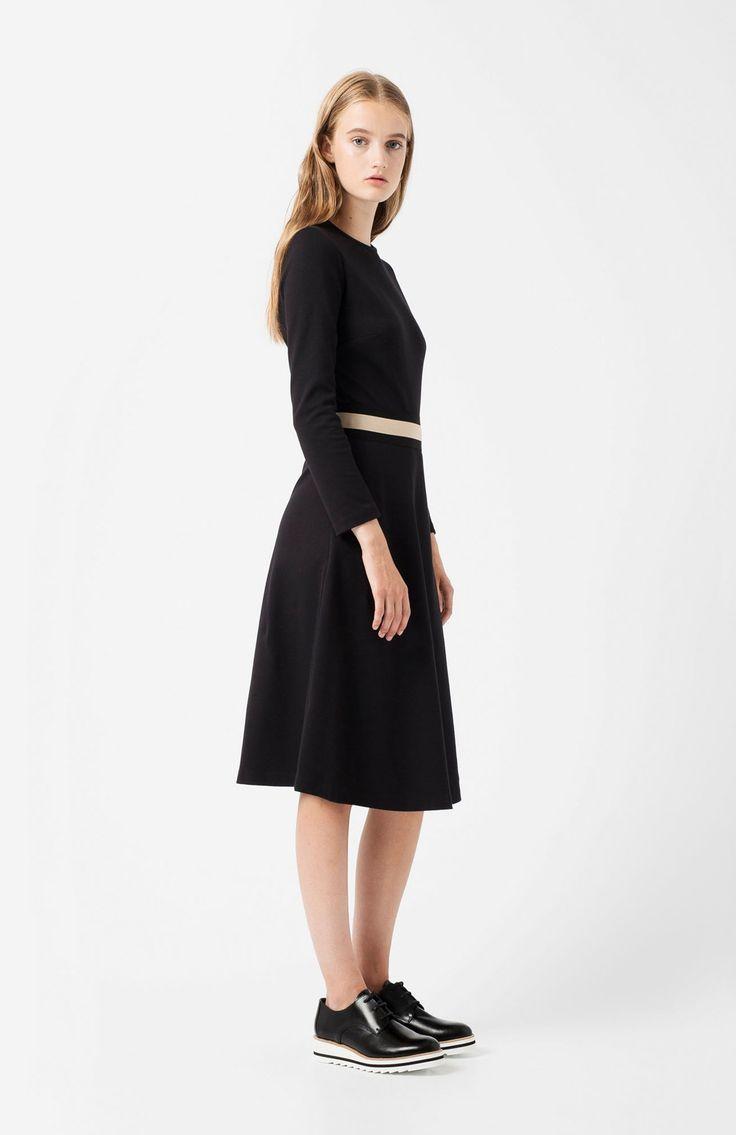 Absti black dress. Below-the-knee black dress, ¾ sleeve, contrasting two-coloured beige elastic and black at the waist. Back zip fastening.