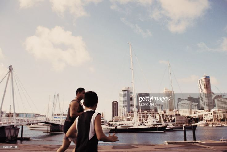 A Pacific Island Man and Boy Plays Rugby against a Cityscape Harbour background. This image is taken at the Waitemata Harbour area of Downtown Auckland, New Zealand.