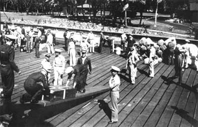 A working party unloads the accumulated gear brought by the 4th Marines to the Philippines.