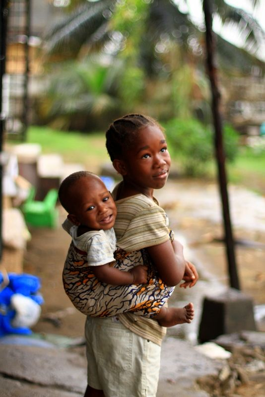 """Liberian child carrying a baby in a traditional """"lapa"""""""