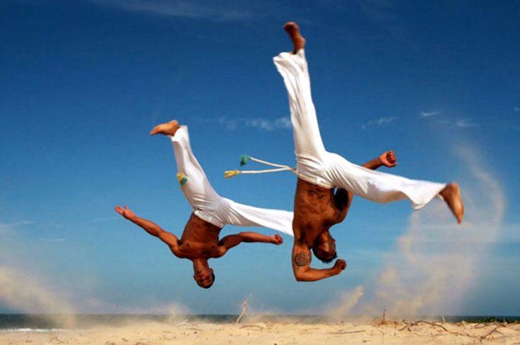 Mistura de dança com luta, a Capoeira tem sua origem na África, trazida ao Brasil pelas mãos dos escravos, como forma de defesa. Ao som ritmado e bem marcado do berimbau de barriga, caxixi, atabaque, pandeiro e reco-reco, dois participantes ensaiam coreografias sincronizadas, gingadas de perna, braços, mãos, pés, cabeça e ombros. O repertório abrange chutes e piruetas cheios de molejo, malícia e manemolência.