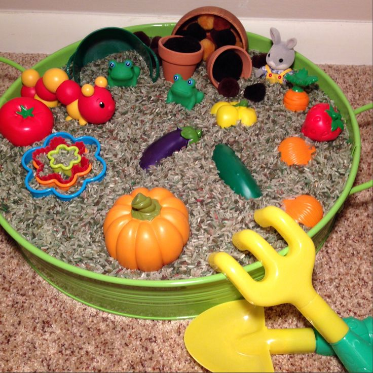Spring Garden Sensory Bin , safe for babies under 2 -- dyed rice, play food and little toy characters buried at various depths, different small containers from the garden store, cookie cutters and silicone baking cups for the flower, brown pom poms, shovel & rake found in the beach toy section. Easy and fun baby play !!