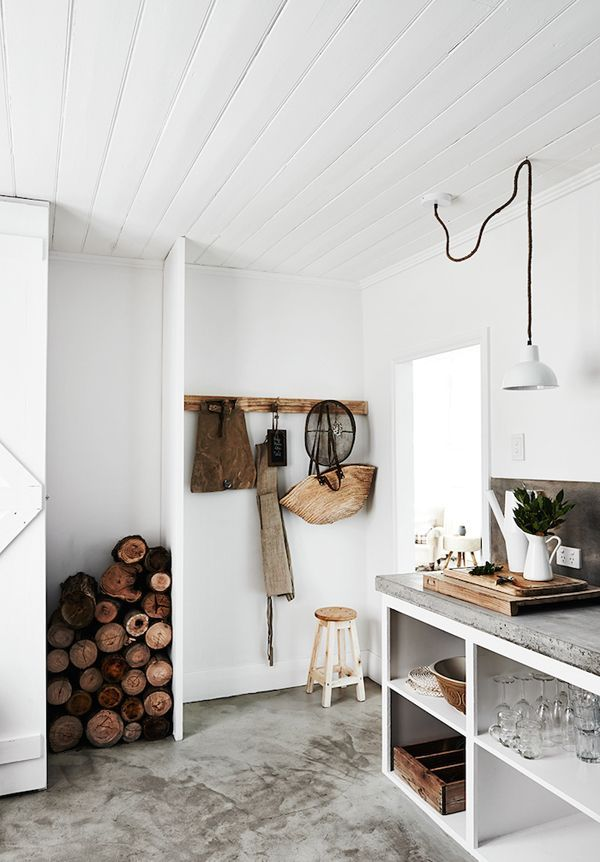 Cozy rustic kitchen with concrete floors, white shiplap walls and firewood /