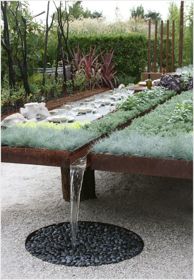 a raised bed with rain water collector and dining table wow