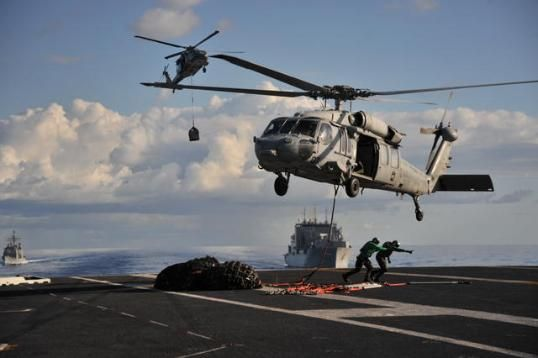 Sailors aboard carrier USS George Washington (CVN 73) clear tarea after attaching cargo nets to MH-60S Seahawk of Helicopter Sea Combat Squadron (HSC) 25 during replenishment-at-sea with Military Sealift Command dry cargo & ammunition ship USNS Charles Drew(T-AKE 10)in Coral Sea,Aug.4,2013.George Washington & embarked air wing, Carrier Air Wing 5,protected maritime interests of U.S,allies & partners in the Indo-Asia-Pacific region.(DoD  Mass Comm Spec 3rd Class Paolo Bayas,USN)