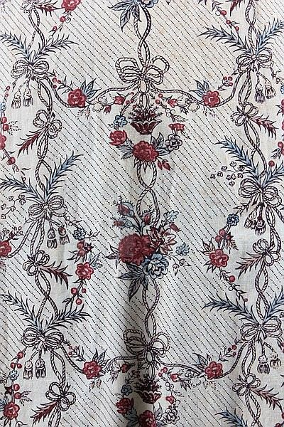 A printed cotton 'Indienne' robe, French, the fabric 1770s but altered into a closed-robe circa 1780-90, the block printed cotton with vertical bands of baskets of fruits, roses and ribbons in shades of red, blue and brown, with closed-front bodice, the waist cut high at the back, the skirt panels stitched closed at the centre front and with apron-like fall with ties to fasten, chest approx 92cm, 36in