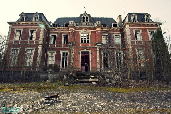 This abandoned mansion in the Auvergne region of France, with decorative turrets above and to either side of the main door, was once clearly the grand country seat of a prosperous family. While the front door remains open for urban explorers and the outer shell appears to be intact, the central upstairs window appears to reveal a gaping hole in the roof, reflecting the fate of so many grand properties left to the elements. The abandoned building is surrounded by other crumbling structures